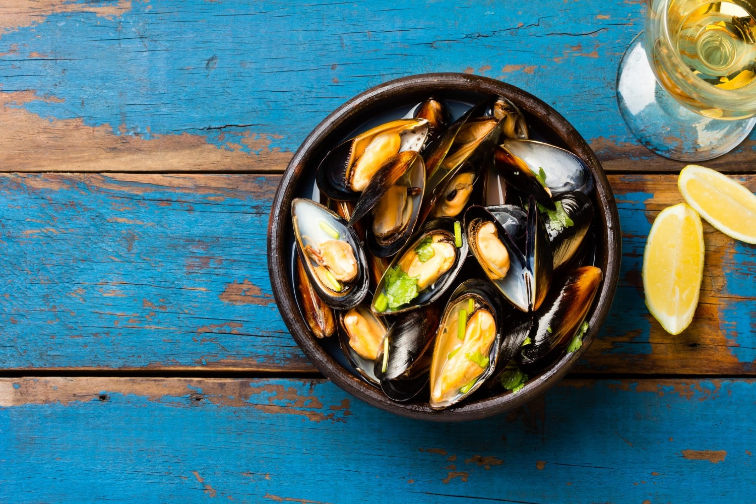 Bowl of mussels on a blue picnic table