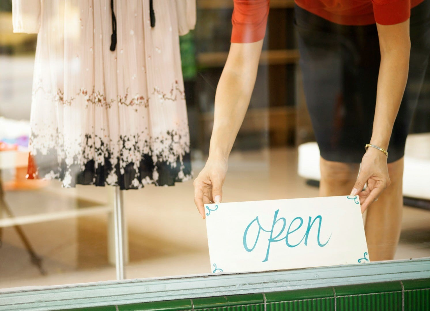 "Woman's hands displaying ""Open"" sign in storefront window,"