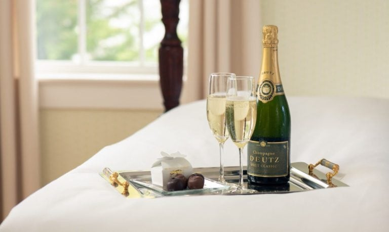 Two glasses of Champagne and a bottle on a silver tray sitting on a bed at Candleberry Inn
