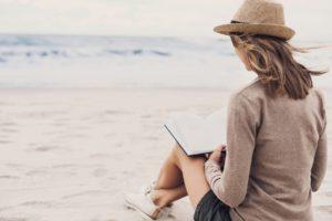 Woman reading a book on a cloudy beach.