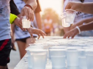 Runners grabbing marathon cups during a race.