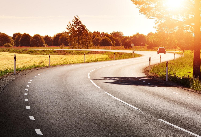 Car driving down winding road at sunset.