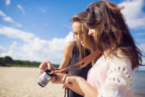 Two female friends watching photos on camera on beach