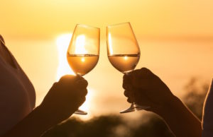 Couple toasting glasses at sunset
