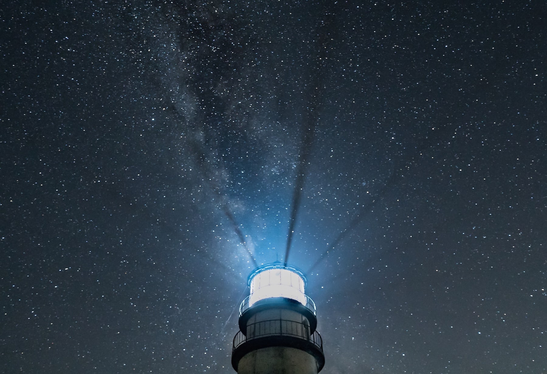 Lighthouse at night with radiating beams and starry sky with Milky Way