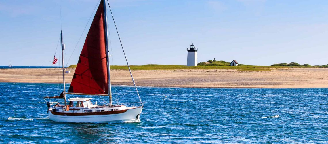 sailboat on ocean with lighthouse in background