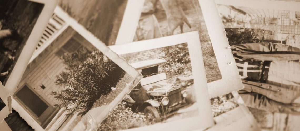 Old black and white photos spread out on table.