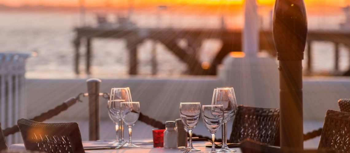Table set with glasses overlooking an ocean view.
