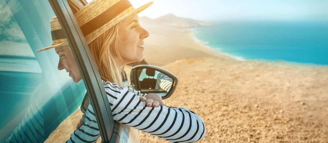 Woman sitting in a car looking out at the ocean.