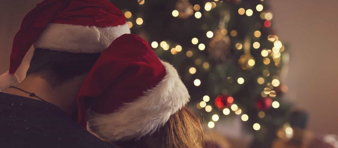 Couple with Santa hats on sitting by a Christmas tree.