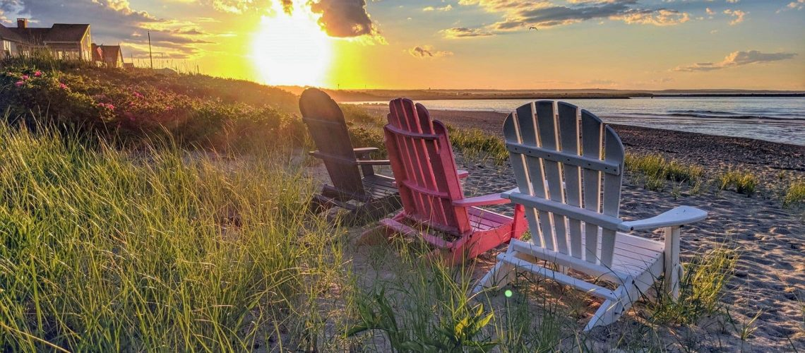 Beach chairs on sand with sunset in the background.