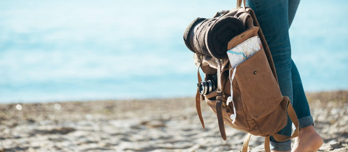 Woman traveler stand on the sand beach and holding backpack.