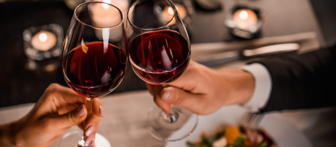 Close up of young couple toasting with glasses of red wine at restaurant